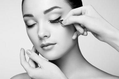 Makeup artist glues eyelashes