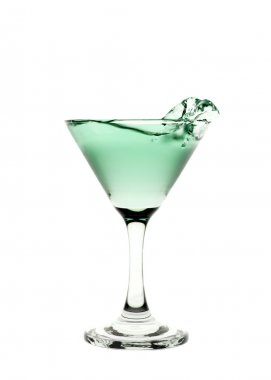 Green liquid splashing in a martini glass isolated on white back