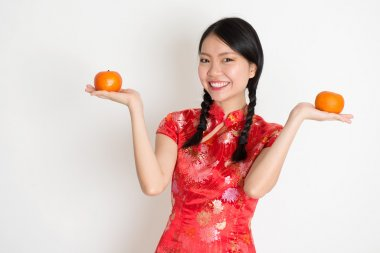 Portrait of Asian Chinese girl hands holding tangerine orange, in traditional red qipao standing on plain background. stock vector