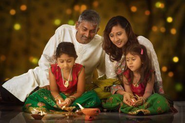 Indian family in traditional sari lighting oil lamp and celebrating Diwali, fesitval of lights inside a temple. Little girl hands holding oil lamp indoors. stock vector