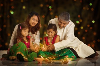 Indian family in traditional sari lighting oil lamp and celebrating Diwali or deepavali, fesitval of lights at home. Little girl hands holding oil lamp indoors. stock vector