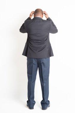 Back side full length mature Indian businessman thinking