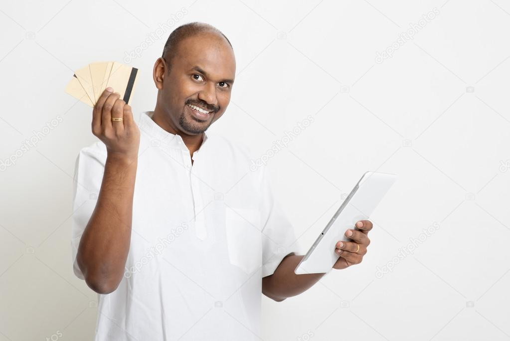 Mature casual business indian man online payment stock photo portrait of mature casual business indian man using digital tablet pc and credit card for online purchase standing on plain background with shadow reheart Images