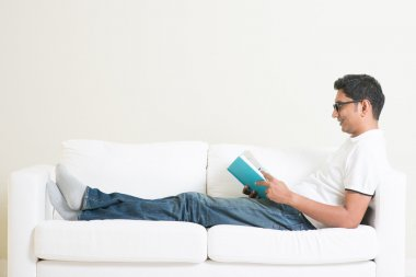 Asian man reading book on couch