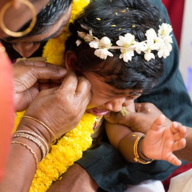 Baby girl crying during the karnavedha events. Traditional Indian Hindus ear piercing ceremony. India special rituals. stock vector
