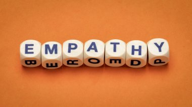 empathy word abstract in dice letters against handmade orange paper, the ability to understand and share the feelings of another