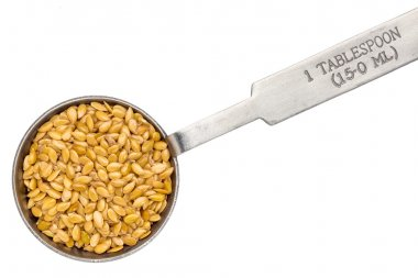 golden flax seed on measuring spoon