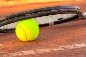 tenisový míček a raketu na tenis antukové hřiště