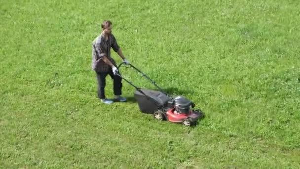 Pohled shora na mužského dělníka sekajícího zelený trávník s motorizovanou sekačkou. Zahradní služby, zahradní údržba.