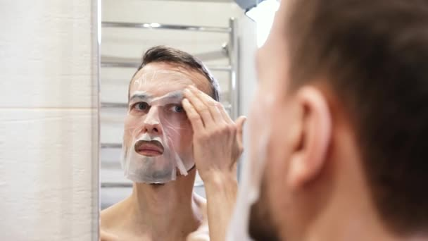Zrcadlový odraz usmívajícího se mladého vousatého muže odstraní kosmetickou obličejovou masku z obličeje a vychutná si výsledný efekt na pokožku. Vlastní péče, wellness a lázeňská léčba doma.