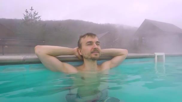 Geotermální lázně. Pohledný muž odpočívající v horkém jarním bazénu venku v horách. Koupání v horké vodě, mimosezónní turistická atrakce. Koncept wellness a vlastní péče.