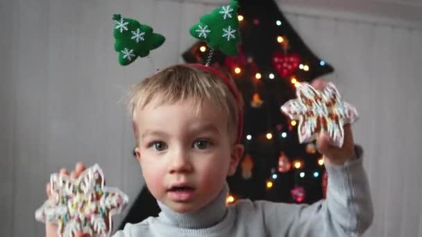 Christmas child boy portrait. Fröhlich-lustiges Kind bedeckt seine Augen mit weihnachtlichen Lebkuchen und hat Spaß in der Nähe des alternativen Weihnachtsbaums.