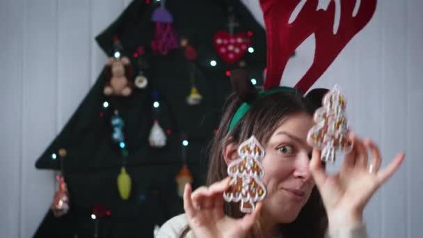 Portrét Vánoční ženy. Veselý legrační dívka zakrýt její oči s x-mas perník cookies a baví poblíž alternativní vánoční strom.