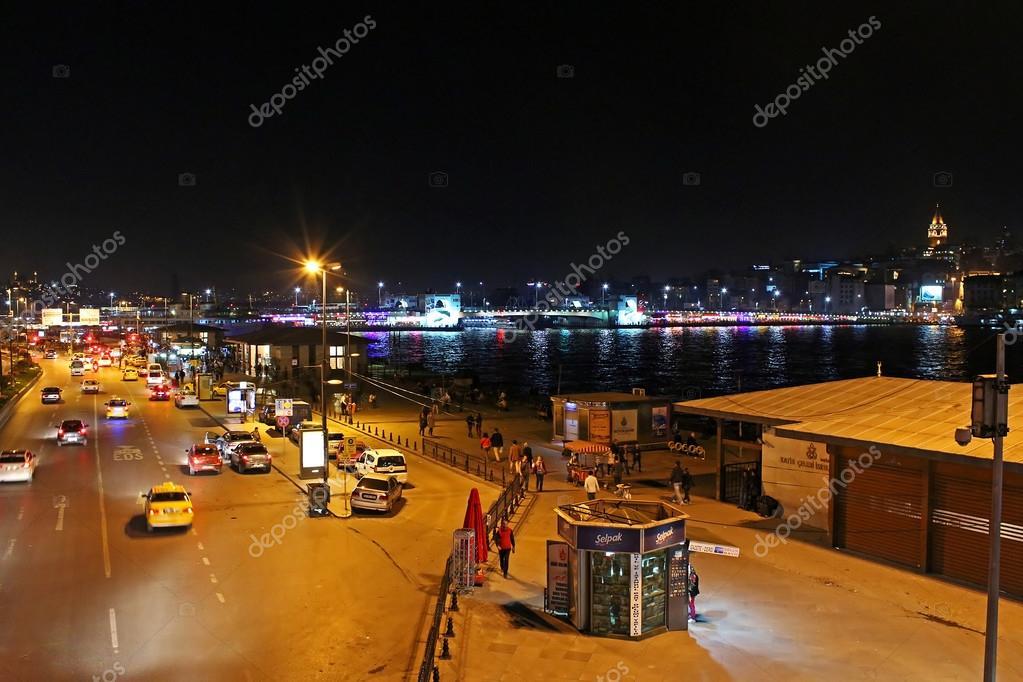 view over traffic next to eminonu pier and galata bridge at night in