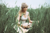 Fotografie young woman sitting on a field and playing guitar