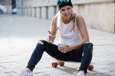 Hipster skater girl in city using cell phone stock vector