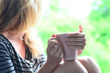 Cute blonde sitting on the windowsill and looking out the window with cup of coffee in the morning