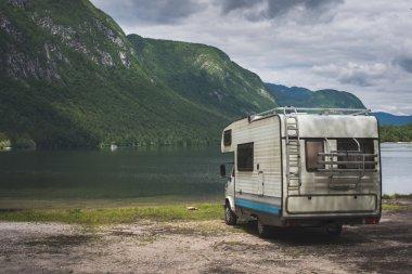 Camper van parked on a beach, mountain range landscape
