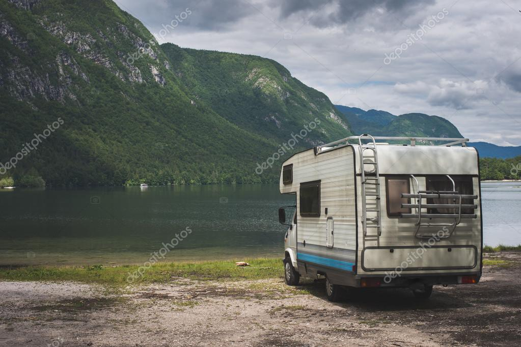 Camper van parked on a beach, mountain range landscape
