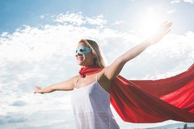 Young woman posing as superhero over blue sky stock vector