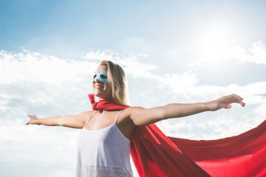 Blonde superhero standing over blue sky and arms outstreched