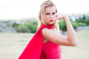 Confident blonde woman in red costume showing muscle and strength