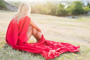 Blonde super hero resting in sunset wearing red mantle and red costume