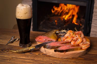 Glass of dark beer and a fish platter on the background of a bur