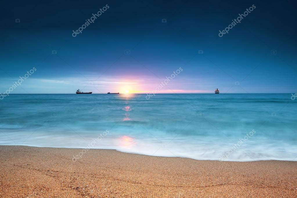 Cargo ship sailing on sunrise near the beach