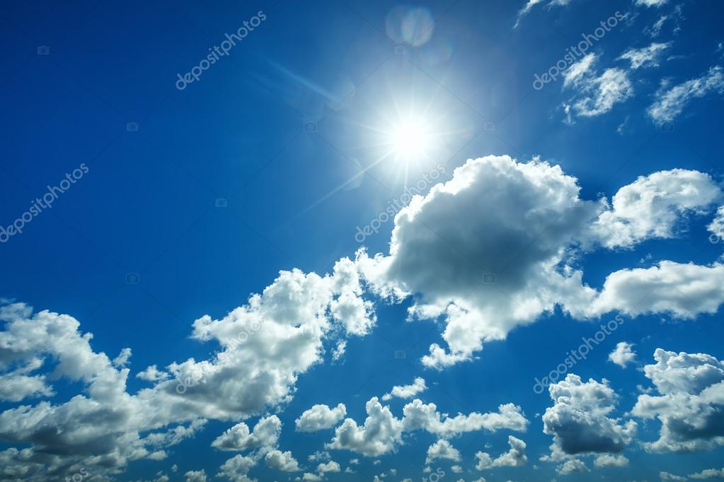 beautiful blue sky with white fluffy clouds and sun