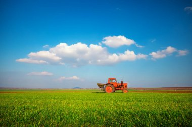 Tractor fertilizing wheat field