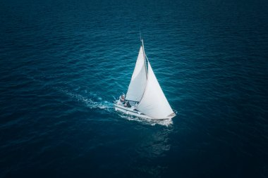 Sailing ship yacht with white sails at opened sea. Aerial - drone view to sailboat in windy condition.