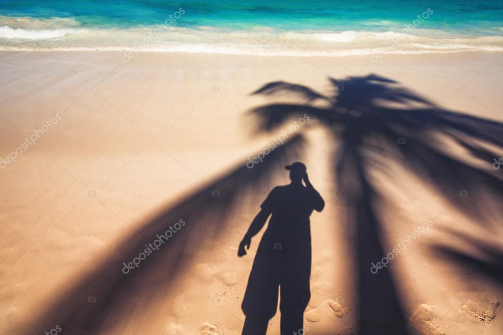 Man and palm tree shadows on tropical white sand beach