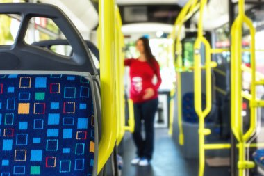 Pregnant woman travelling with public autobus or tramway, during