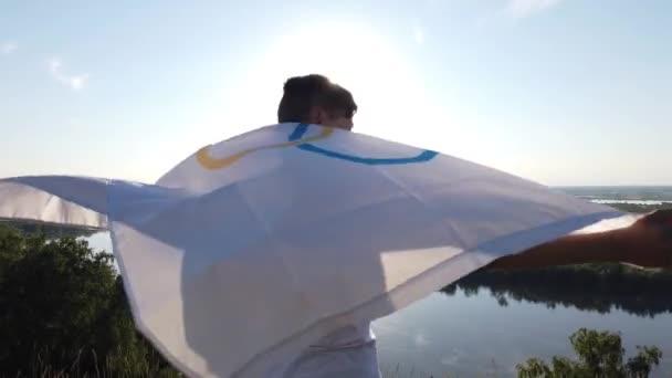 Junge schwenkt Fahne bei den Olympischen Spielen im Freien