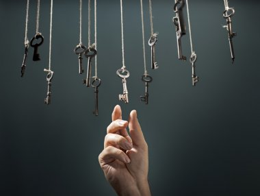 Hand choosing a hanging key