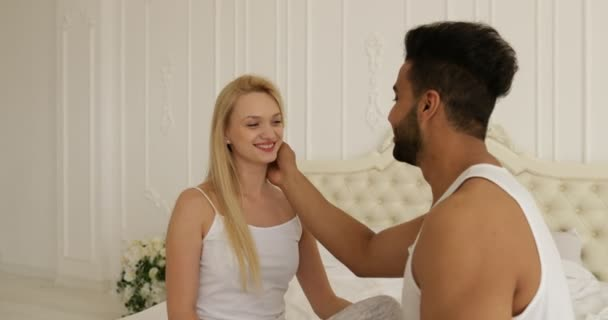 Pár lásky objetí úsměv sedací postel tváří v tvář mix rasy člověka dotýká žena tvář objetí ráno ložnice