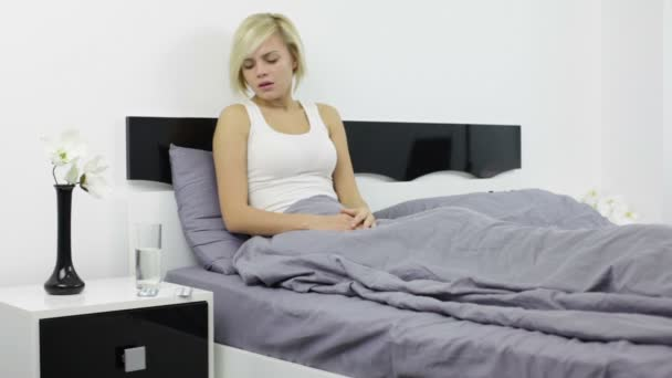 Woman taking pill in bed