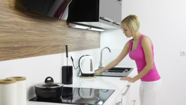 Mladá žena čištění kuchyňské linky