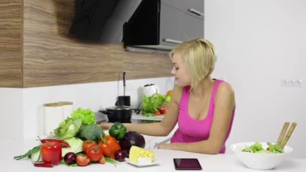 Woman using tablet computer to prepare dinner
