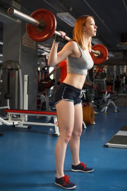 Young strong girl do squats with a barbell