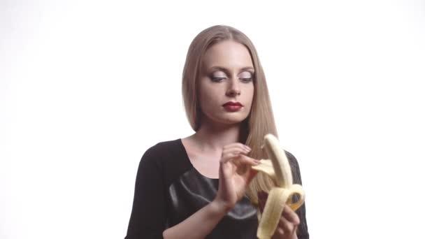 Krásná mladá žena s červenými rty jíst banán