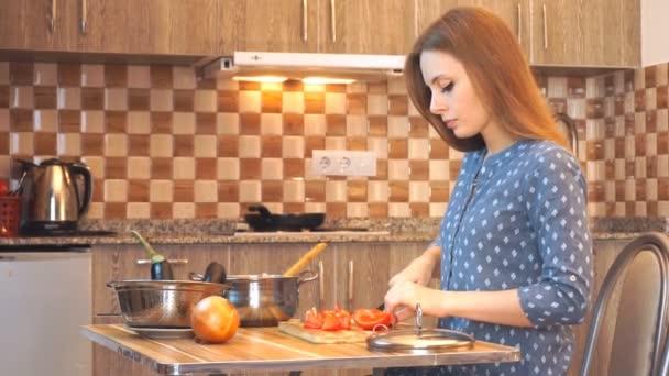 Životní styl v zdravých potravinách: krásná žena, která příležitostně vaří, v kuchyni krájí zeleninu. Střední záběr, přenosný, pomalý pohyb 60 fps.