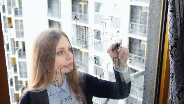 Életmód: szép fiatal nő rajz matematikai üzleti grafikonok az üveg felhőkarcoló a háttérben. Balkezem. Közepes méretű, kézi, lassított 60 fps.