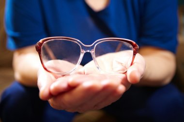 Old woman hands with eyeglasses