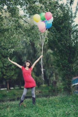 Happy young pregnant woman with balloons in the hands
