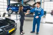 Fotografie mechanika dává klíč od auta na klienta