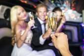 Bohatí lidé pít šampaňské v limuzíně