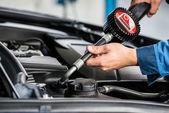 Mužské mechanik ruce plnění olej do auta