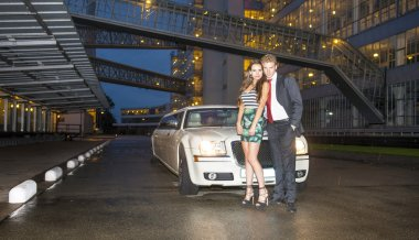 Cute couple in front of a limousine